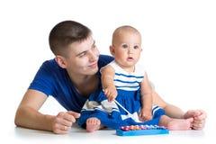 Vader en babymeisje die pret met muzikaal speelgoed hebben stock afbeeldingen