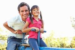 Vader en de Dochter die de berijden op zien Zaag in Playgroun stock foto's