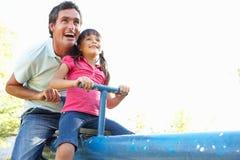 Vader en de Dochter die de berijden op zien Zaag in Playgroun stock afbeeldingen