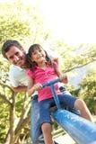 Vader en de Dochter die de berijden op zien Zaag in Playgroun stock afbeelding