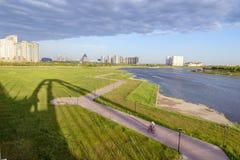 Vader en dochter berijdende fietsen langs de rivier naar stad Ta stock foto's