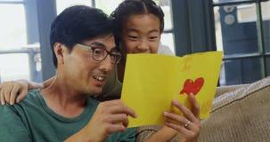 Vader en dochter de kaart van de lezingsgroet in woonkamer 4k stock footage