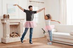 Vader en dochter in de roze rokken die van tututulle samen thuis dansen Stock Afbeeldingen