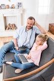 Vader en dochter die apparaten met behulp van stock foto