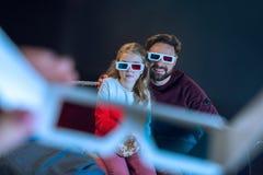 Vader en dochter die in 3d glazen op bank zitten Stock Afbeeldingen