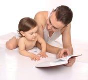 Vader en dochter die een boek lezen Stock Afbeeldingen
