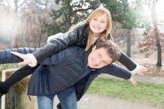 Vader en dochter die een pretvervoer per kangoeroewagen in het parkfamilie van de de herfstwinter hebben royalty-vrije stock afbeeldingen