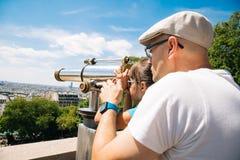 Vader en dochter die een telescoop in Parijs gebruiken Stock Foto