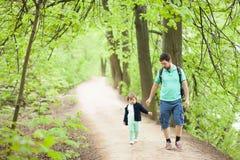 Vader en dochter die in het park lopen Stock Afbeeldingen