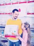 Vader en dochter die hun aankoop van kanarievogel opscheppen royalty-vrije stock fotografie