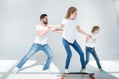Vader en dochter die jong vrouwen berijdend skateboard helpen royalty-vrije stock foto's