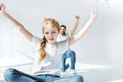 Vader en dochter die met opgeheven handen op grijs toejuichen stock foto's
