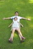 Vader en dochter die op een weide samen liggen royalty-vrije stock afbeelding