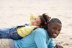 Vader en dochter die op strand leggen Royalty-vrije Stock Afbeeldingen