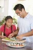 Vader en Dochter die Sushi samen voorbereiden royalty-vrije stock afbeeldingen