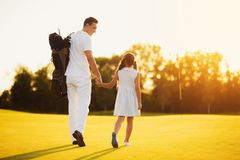 Vader en dochter die tegen de zonsondergang over de golfcursus lopen Zij worden gedraaid met hun ruggen naar de camera royalty-vrije stock foto's