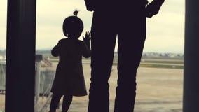 Vader en dochter die uit het venster met mening over luchthavengebied kijken De vliegtuigen kunnen in de afstand worden gezien stock video