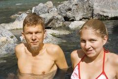 Vader en dochter die van een hete rotspool genieten stock fotografie