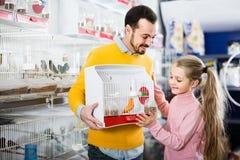 Vader en dochter die van hun aankoop van kanarievogel genieten in pe stock foto
