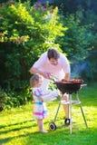 Vader en dochter die vlees roosteren Stock Afbeeldingen