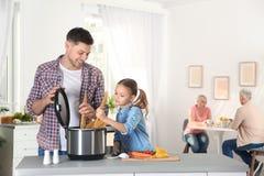 Vader en dochter die voedsel met modern multikooktoestel voorbereiden stock afbeeldingen