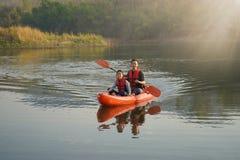 Vader en dochter het roeien boot op kalme wateren royalty-vrije stock fotografie