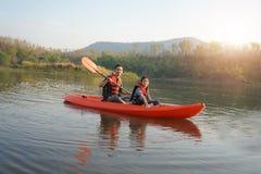 Vader en dochter het roeien boot op kalme wateren stock foto's