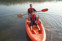 Vader en dochter het roeien boot op kalme wateren stock foto