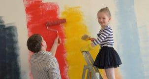 Vader en dochter het schilderen muren in helder stock videobeelden