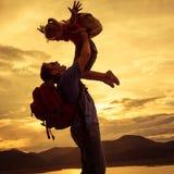 Vader en dochter het spelen op de kust van meer bij de zonsondergang t Stock Foto