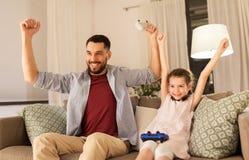 Vader en dochter het spelen videospelletje thuis royalty-vrije stock fotografie
