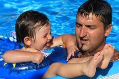 Vader en dochter in het zwembad stock afbeeldingen