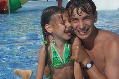 Vader en dochter in het zwembad stock foto's