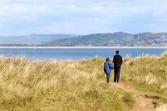 Vader en dochter op gang langs de kust stock foto's