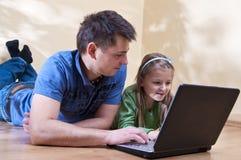 Vader en dochter op laptop royalty-vrije stock afbeelding