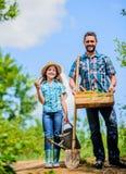 vader en dochter op rancho De zomer de landbouw landbouwersmens met meisje tuinhulpmiddelen, schop en gieter kid royalty-vrije stock afbeelding