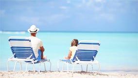 Vader en dochter op strandzitting op chaise-longue stock footage