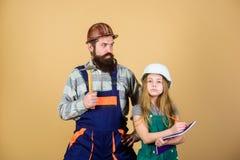 Vader en dochterbouwvakkerhelm eenvormig het vernieuwen huis Het huisverbetering activiteit Jong geitjemeisje planningsvernieuwin stock foto's