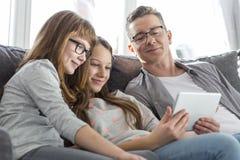 Vader en dochters die tabletpc op bank thuis met behulp van Royalty-vrije Stock Foto's
