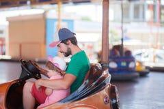 Vader en jong geitje die pret, themapark hebben Stock Foto's