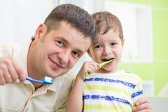 Vader en jong geitje het borstelen tanden in badkamers Royalty-vrije Stock Foto's