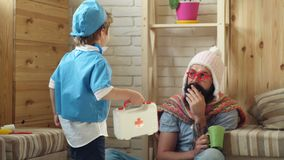 Vader en jong geitje het spelen kliniek Mens in gebreide witte hoed en kleurrijke sjaalzitting op vloer met hete geneeskunde geba stock video