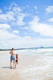 Vader en jonge dochter die langs strand lopen Stock Afbeelding