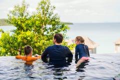 Vader en jonge geitjes bij zwembad Royalty-vrije Stock Afbeeldingen