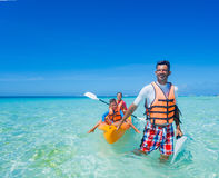 Vader en jonge geitjes die bij tropische oceaan kayaking stock afbeeldingen