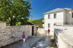 Vader en jonge geitjes die Monodendri-dorp met zijn traditionele stenen-gemaakte gebouwen en steengangen onderzoeken, Zagoria-geb stock afbeeldingen