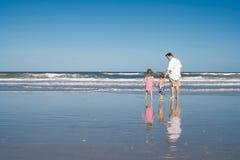 Vader en jonge geitjes op een strand Royalty-vrije Stock Foto