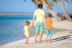 Vader en jonge geitjes op een strand Stock Afbeelding