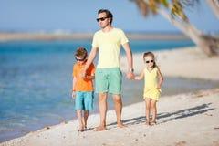 Vader en jonge geitjes op een strand Stock Foto's