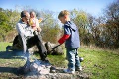 Vader en jonge geitjes op picknickplaats Stock Fotografie